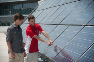 Travis Tippens works with solor panels on top of the FREEDM Center on Centennial Campus. Photo by Marc Hall